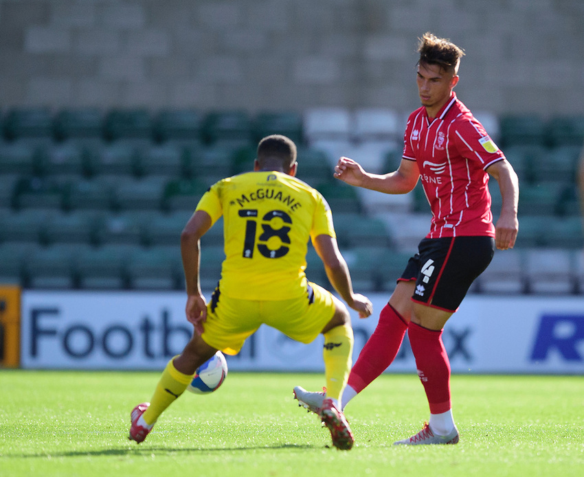 Lincoln City's Lewis Montsma clears under pressure from Oxford United's Marcus McGuane<br /> <br /> Photographer Andrew Vaughan/CameraSport<br /> <br /> The EFL Sky Bet League One - Saturday 12th September  2020 - Lincoln City v Oxford United - LNER Stadium - Lincoln<br /> <br /> World Copyright © 2020 CameraSport. All rights reserved. 43 Linden Ave. Countesthorpe. Leicester. England. LE8 5PG - Tel: +44 (0) 116 277 4147 - admin@camerasport.com - www.camerasport.com - Lincoln City v Oxford United