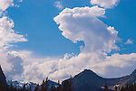 A cloud, shaped as a shark, floats high above the mountains in the Canadian Rocky Mountains.