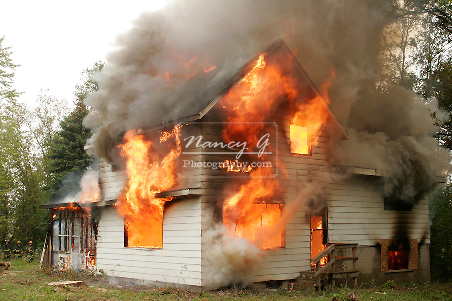 House on fire with flames coming out the windows