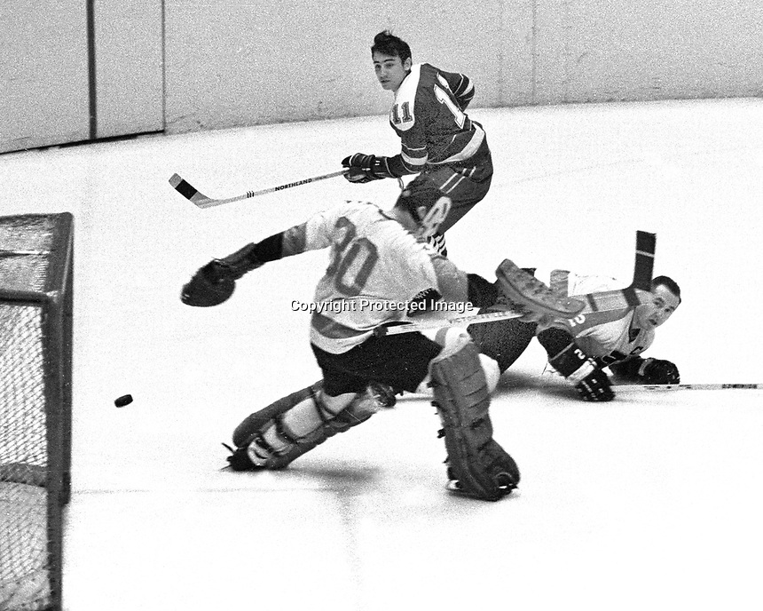 Seals vs Flyers:.Seals #11 Don O'Donoghue fires the puck past Flyer goalie #30 Bernie Parent, Ed Van Impe lying on the ice..(photo by Ron Riesterer)
