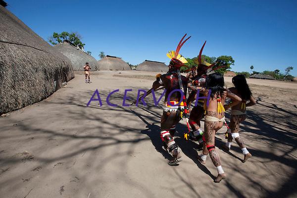 Cerim&ocirc;nia do Kwarup na aldeia Kamaiur&aacute;, no Parque ind&iacute;gena Xingu.<br /> <br /> O Kwarup (nome do ritual na l&iacute;ngua kamaiur&aacute;) &eacute; considerado o grande emblema do Alto Xingu e trata-se de uma cerim&ocirc;nia funer&aacute;ria, que envolve mitos de cria&ccedil;&atilde;o da humanidade, a classifica&ccedil;&atilde;o hier&aacute;rquica nos grupos, a inicia&ccedil;&atilde;o das jovens e as rela&ccedil;&otilde;es entre as aldeias. Ao longo dos meses que se seguem at&eacute; o encerramento ocorrem, n&atilde;o necessariamente todos os dias, dois tipos de dan&ccedil;as e o toque de longas flautas (uru&aacute;, na l&iacute;ngua dos Kamaiur&aacute;), sempre retribu&iacute;dos com oferecimento de alimentos pelos &ldquo;donos&rdquo; do Kwarup. O foco de orienta&ccedil;&atilde;o dessas atividades rituais &eacute; sempre a cerca sobre a sepultura. No p&aacute;tio da aldeia promotora do rito, cada falecido homenageado &eacute; representado por uma se&ccedil;&atilde;o de tronco de cerca de dois metros. S&atilde;o de uma esp&eacute;cie vegetal que tem distintas denomina&ccedil;&otilde;es conforme as diferentes l&iacute;nguas xinguanas. Os Kamaiur&aacute; a chamam de Kwarup, a mesma madeira com que o her&oacute;i m&iacute;tico fez as mulheres que enviou para se casarem com o jaguar. Os troncos s&atilde;o colocados um ao lado do outro, de p&eacute;, embutidos em buracos de 50 cm de fundo. S&atilde;o pintados e ornamentados com adornos plum&aacute;rios e cintos masculinos. A &uacute;nica distin&ccedil;&atilde;o entre os troncos que representam homens e os que representam mulheres &eacute; que os primeiros s&atilde;o guarnecidos com mechas de algod&atilde;o n&atilde;o fiado. Tamb&eacute;m os homens comuns falecidos t&ecirc;m direito a ser representados por troncos, por&eacute;m menos grossos e com ornamenta&ccedil;&atilde;o mais simples. Os esp&iacute;ritos dos mortos homenageados ficam junto aos troncos na &uacute;ltima noite do rito e a isto se reduz 