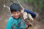 A Guarani indigenous boy carries firewood in Choroquepiao, a small village in the Chaco region of Bolivia. Church World Service works with families in the village to improve the quality of their lives.