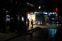 Evening landscape view of the silhouettes of two women standing in front of a storefront near Shi Li Da Dao in the Lúshān Qū of Jiǔjiāng in Jiangxi Province.  © LAN