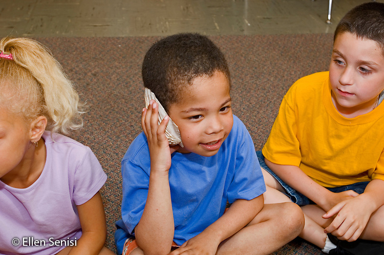 Schenectady, NY.Zoller School (urban public elementary school).Student (boy, 6, African-American / Caucasian) holds shell against his ear during language arts lesson where students hold shells then talk about them..MR: Jam4.© Ellen B. Senisi