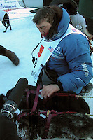 John Baker pets his dogs after finishing eighth in the 2007 Iditarod. Photo by Jon Little.