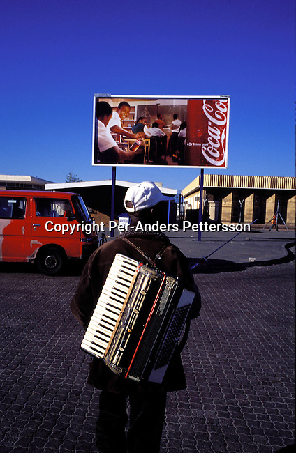dimubus00014 Buskers. An unidentified musician carrying a accordion after playing o the street on August 10, 2001 in Site C Khayelitsha, a township about 35 kilometers outside Cape Town, South Africa. Khayelitsha is one of the poorest and fastest growing townships in South Africa. People usually come from the rural areas in Eastern Cape province to find work as maids and laborers. Most people don't find work and the unemployment rate is very high, together with lot of violence and a growing HIV-Aids epidemic itÕs a harsh area to live in..©Per-Anders Pettersson/ iAfrika Photos.