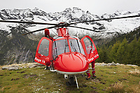 "Switzerland. Canton Ticino. Chironico valley. Intermediate landing for a Rega Agusta AW109 SP Grand ""Da Vinci"" helicopter on a rescue mission. All Rega helicopters carry a crew of three: a pilot Corrado Sasselli (L), an emergency physician, and a paramedic Paolo Menghetti (R) who is also trained to assist the pilot for radio communication, navigation, terrain/object avoidance, and winch operations. The pilot and the paramedic wait for a radio call from the emergency doctor, who has been winched down on the ground to give the prime cure at an injured hiker. The name Rega was created by combining letters from the name ""Swiss Air Rescue Guard"" as it was written in German (Schweizerische Rettungsflugwacht), French (Garde Aérienne Suisse de Sauvetage), and Italian (Guardia Aerea Svizzera di Soccorso). Rega is a private, non-profit air rescue service that provides emergency medical assistance in Switzerland. Rega mainly assists with mountain rescues, though it will also operate in other terrains when needed, most notably during life-threatening emergencies. As a non-profit foundation, Rega does not receive financial assistance from any government. People in distress can call for a helicopter rescue directly (phone number 1414). The AgustaWestland AW109 is a lightweight, twin-engine, helicopter built by the Italian manufacturer Leonardo S.p.A. (formerly AgustaWestland, Leonardo-Finmeccanica and Finmeccanica). Leonardo S.p.A is an Italian global high-tech company and one of the key players in aerospace. In close collaboration with the manufacturer, the Da Vinci has been specially designed to cater for Rega's particular requirements as regards carrying out operations in the mountains. It optimally fulfills the high demands made of it in terms of flying characteristics, emergency medical equipment and maintenance. Safety, performance and space have been increased, and maintenance and noise emissions reduced. The Chironico valley is a valley lateral to the Levantina valley. 10"