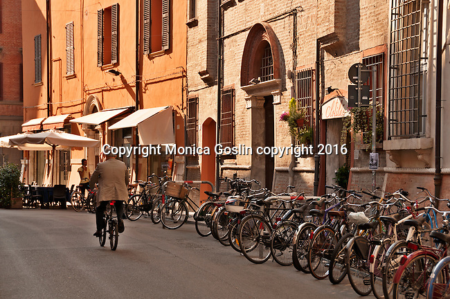 A man rides a bike down a street in Historic Old Town lined with bikes