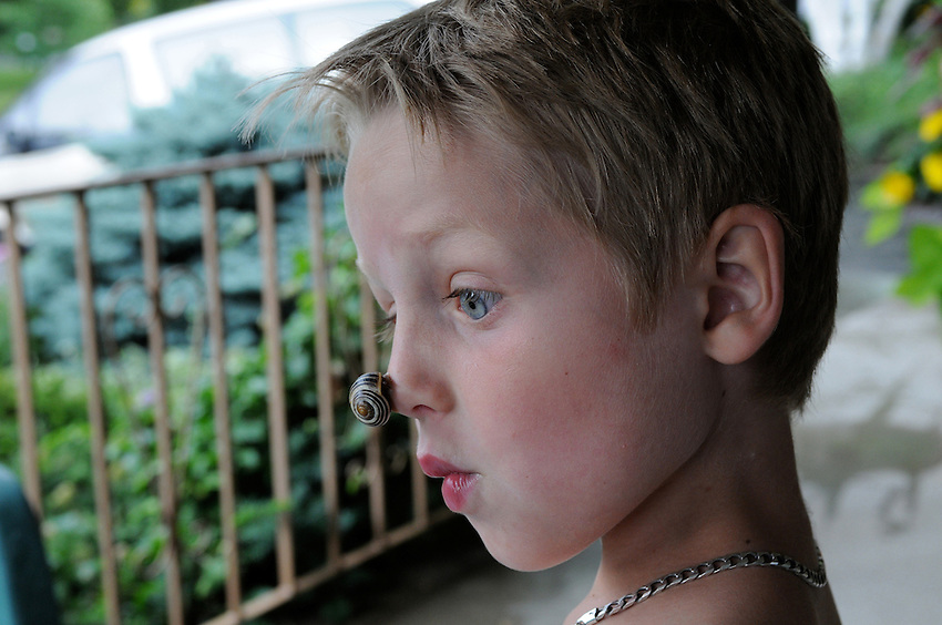 A boy with a snail on his nose, nature's version of a clown nose