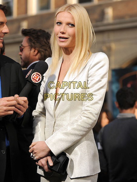 GWYNETH PALTROW.The Marvel World Premiere of Iron Man 2 held at The El Capitan Theatre in Hollywood, California, USA..April 26th, 2010      .half length white  shiny jacket blazer black clutch bag mesh shoulder pads mouth open interview microphone .CAP/RKE/DVS.©DVS/RockinExposures/Capital Pictures.