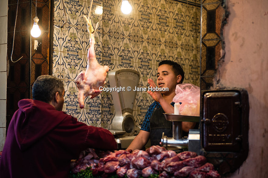 Butcher in the Kasbah area of the Medina, Marrakech, Morocco, selling chicken to a male customer.