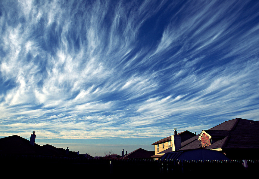 Thin wisps of Cirrus Uncinus clouds (mare's tails) streak across the sky over Norman Oklahoma during late Winter.