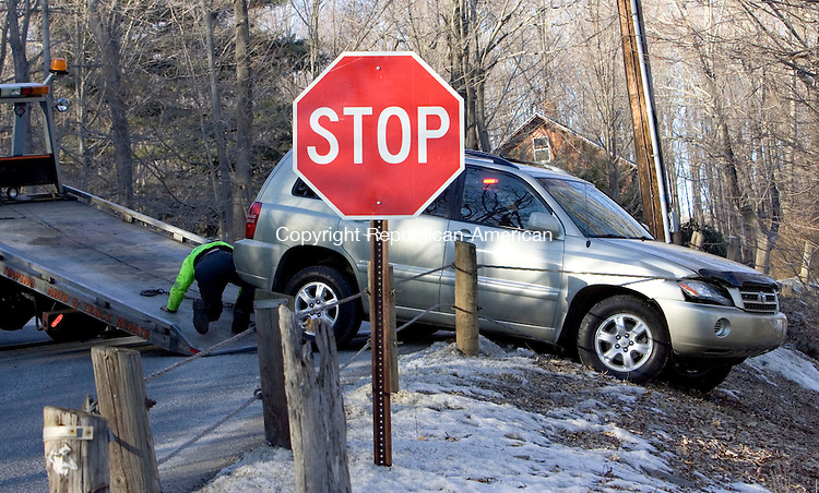 SOUTHBURY, CT- 16 FEB 2008- 021608JT06-<br /> A tow-truck driver secures an SUV to be lifted after it was involved in a one-vehicle accident, driving into the guard wire at the intersection of Stillson and Purchase Brook Roads on Saturday in Southbury.<br /> Josalee Thrift / Republican-American