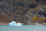 A small iceberg backdropped by the colorful Eastern Greenland landscape.