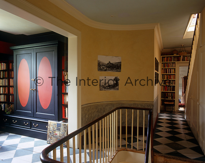 Books are stored on bookshelves build around doorways and in alcoves on the landing