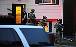 Members of the Spokane SWAT team leave residents of 3918 E 11th Ave at about 6am on Thursday March 13, 2014.