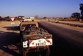"""Near Tabora, Tanzania. Landscape with four wheel drive jeep on a road in rural Tanzania and sign """"End of Tarmac""""."""