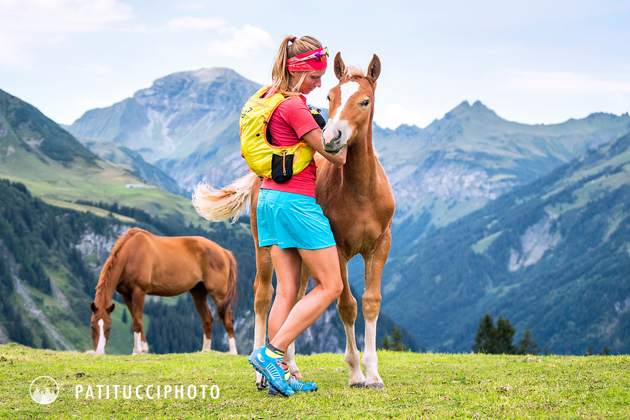 A woman trail runner stops to play with a baby horse above the Weisstannental while on the way to the Pizol, Switzerland