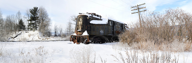 Abandoned railroad locomotive in snow and morning sunlight, PRR GG1 electric.