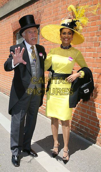 BRUCE FORSYTHE & WILNELIA.Ladies Day at Royal Ascot, Ascot, England, 19th June 2008..full length married husband wife yellow black hat huge dress belt sash top hat suit waistcoat tie hand waving palm.CAP/DS.©Dudley Smith/Capital Pictures