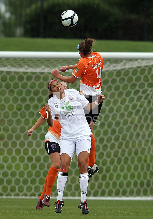 BOYDS, MARYLAND - July 21, 2012:  Amanda Naeher (4) of Charlotte Lady Eagles leaps high over Kimberly DeCesare (6) of the Long Island Roughriders during a W League Eastern Conference Championship semi final match at Maryland Soccerplex, in Boyds, Maryland on July 21.