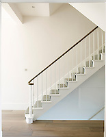 The original Victorian staircase has been given a sculptural quality against clean white walls and an oak floor