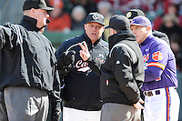 Head coach Chad Holbrook (2) of the South Carolina Gamecocks, second from left, talks with umpires before the Reedy River Rivalry game against the Clemson Tigers on Saturday, February 28, 2015, at Fluor Field at the West End in Greenville, South Carolina. Clemson head coach Jack Leggett is at right. South Carolina won, 4-1. (Tom Priddy/Four Seam Images)