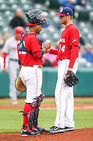 Carlos Corporan (22) talks to pitcher Jordan Lyles (14) during the MiLB matchup between the Memphis Redbirds and the Oklahoma City Redhawks at Chickasaw Bricktown Ballpark on April 8th, 2012 in Oklahoma City, Oklahoma. The Redhawks defeated the Redbirds 8-1  (William Purnell/Four Seam Images)