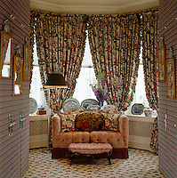 The built-in cupboards in this dressing room are covered in a plaid fabric and colourful chintz curtains dress the bay window behind the two-seater sofa