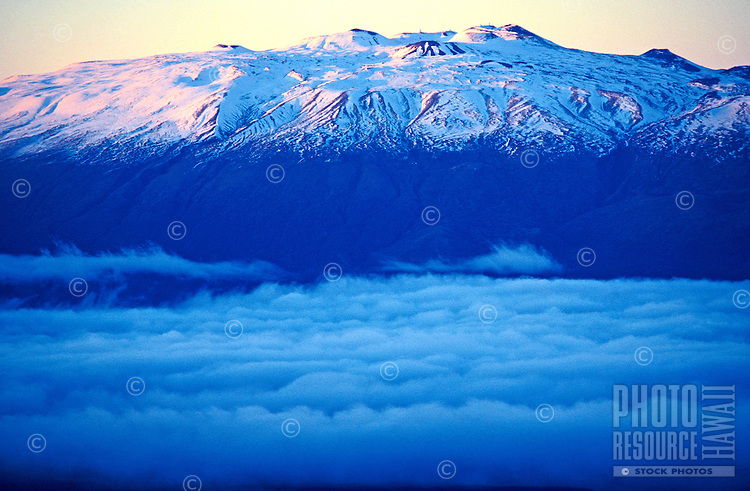 Mauna Kea, upper elevation with snow line, taken from Mauna Loa. Showing clouds hanging in the saddle between Mauna Loa and Mauna Kea.