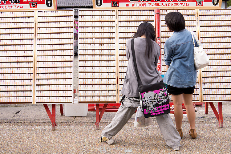 Two girls looking at name-based lucky charms for boys.