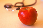 red apple on counter-top next to stethoscope