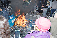 People crowd around as a China Daily newspaper box is set on fire during street demonstrations after the inauguration of President Donald Trump on Jan. 20, 2017, in Washington, D.C.
