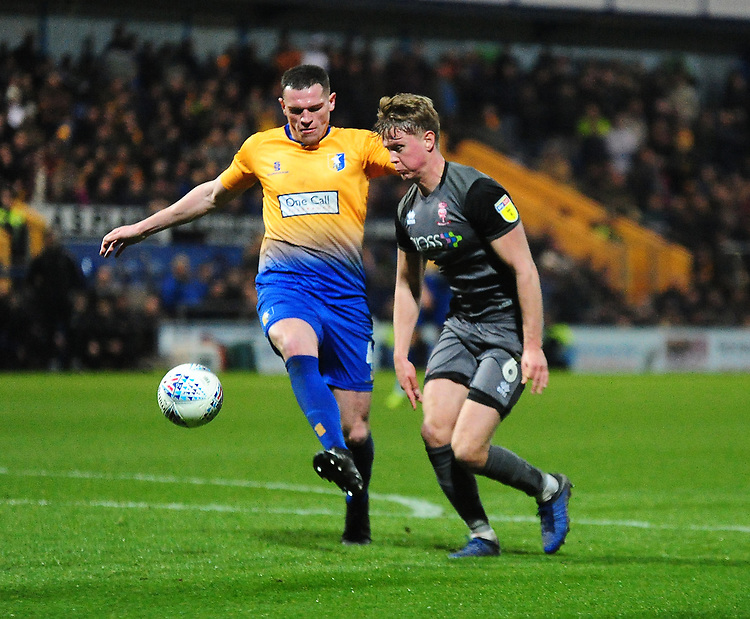 Mansfield Town's Matt Preston clears under pressure from Lincoln City's Mark O'Hara<br /> <br /> Photographer Andrew Vaughan/CameraSport<br /> <br /> The EFL Sky Bet League Two - Mansfield Town v Lincoln City - Monday 18th March 2019 - Field Mill - Mansfield<br /> <br /> World Copyright © 2019 CameraSport. All rights reserved. 43 Linden Ave. Countesthorpe. Leicester. England. LE8 5PG - Tel: +44 (0) 116 277 4147 - admin@camerasport.com - www.camerasport.com