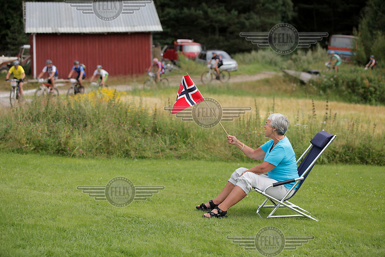 A woman waves a Norwegian flag as she cheers for the riders. Grenserittet is a 80km mountain bike race starting in the Swedish town of Strömstad, ending up in the Norwegian town Halden. The interest for these kind of bike races has exploded in Norway the last few years, particularly with middle age affluent men.