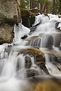 Stair Falls along Bumpus Brook in Randolph, New Hampshire USA surrounded with ice during the spring months. Bumpus Brook has a number of waterfalls on it.