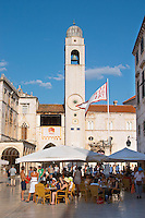 The main street Stradun Placa with traditional houses and flocks of tourists, view cafe terrace with outside seating and over clock tower and loggia Luza on the central square in morning sunlight. The city flag banner with Libertas text Dubrovnik, old city. Dalmatian Coast, Croatia, Europe.