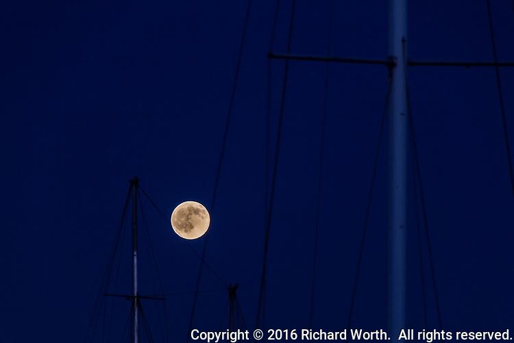 The Full Buck Moon 'balances' on the lines of sailboats moored at the San Leandro Marina on California's San Francisco Bay.