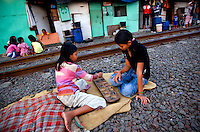 Students of Kartini Emergency School hang out outside their homes next to the railway tracks in North Jakarta. Since the early 1990s, twin sisters Sri Rosyati (known as Rossy) and Sri Irianingsih (known as Rian) have used their family inheritance to set up and run 64 schools in different parts of Indonesia, providing primary education combined with practical skills to some of the country's most deprived children.