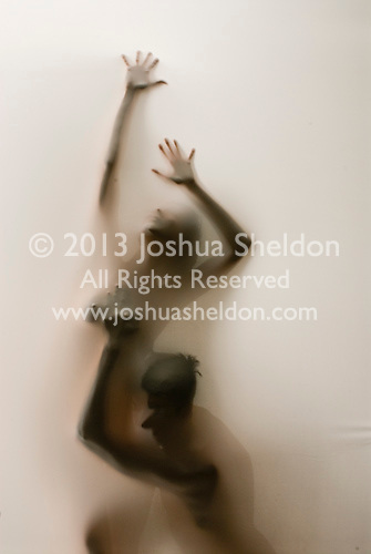 Partially silhouetted man & woman touching behind translucent fabric
