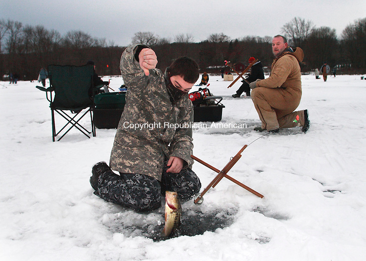 PLYMOUTH, CT- 06 FEBRUARY 2010 020610JW02 - John Wunsch of Plymouth pulls up the first catch of the day as his father John Wunsch looks on during the Terryville Fish and Games Club's annual ice fishing derby Saturday morning.  Jonathan Wilcox Republican-American