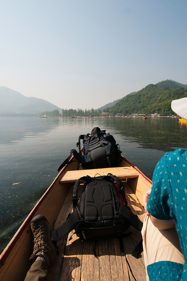 Point of view photograph of travelers and backpacks crossing Dal Lake, Srinagar, Kashmir, India.