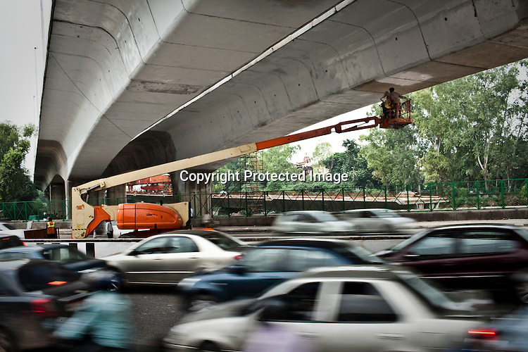 Indian labourers paint the underbelly of the Barapullah Nallah bridge that connects the main stadium to the commonwealth village for the approaching 19th Commonwealth Games 2010 in New Delhi, India.