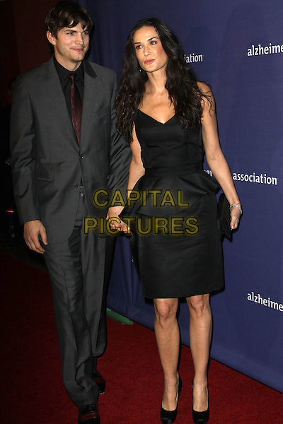 "ASHTON KUTCHER & DEMI MOORE.18th Annual ""A Night at Sardi's"" Benefitting The Alzheimer's Association held At The Beverly Hilton Hotel, Beverly Hills, California, USA..March 18th, 2010.full length grey gray suit black dress holding hands married husband wife peplum clutch bag.CAP/ADM/KB.©Kevan Brooks/AdMedia/Capital Pictures."