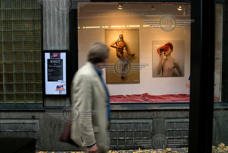 A passer-by looks into the window of Central Saint Martin's College of Art on Charing Cross Road, where photography is on display.