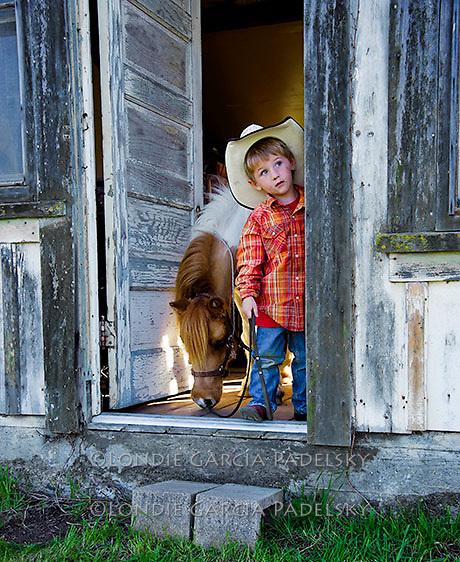 Young cowboy sneaks pony into the ranch bunkhouse. San Luis Obispo, California