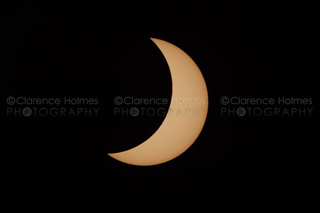 A crescent Sun is visible in the second partial eclipse phase of the Great American Eclipse on August 21, 2017.  Sunspots are visible on the sun's surface.
