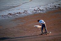 Man painting on beach.