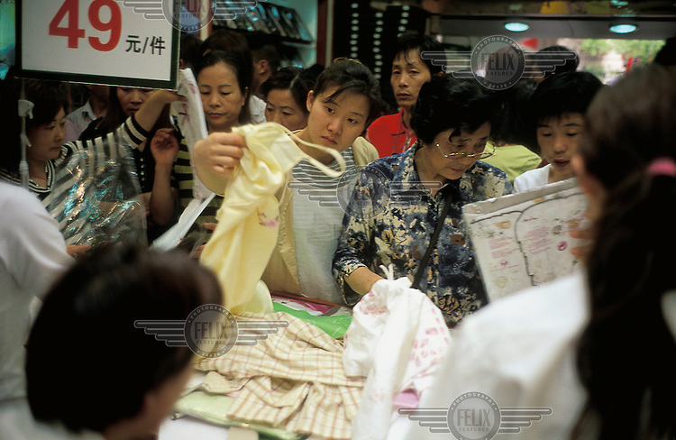 Shoppers sorting through clothes in a shopping mall.
