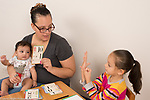 Mother holding 4 month old baby working with daughter using math flash cards, first grade homework, girl using fingers to count